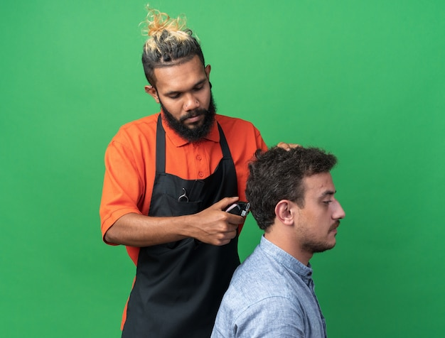 Concentrated young male barber wearing uniform doing haircut for his young client isolated on green wall