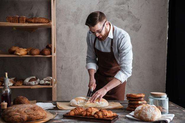Концентрированный молодой человек пекарь нарезать хлеб.