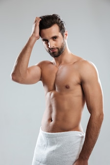Concentrated young man dressed in towel