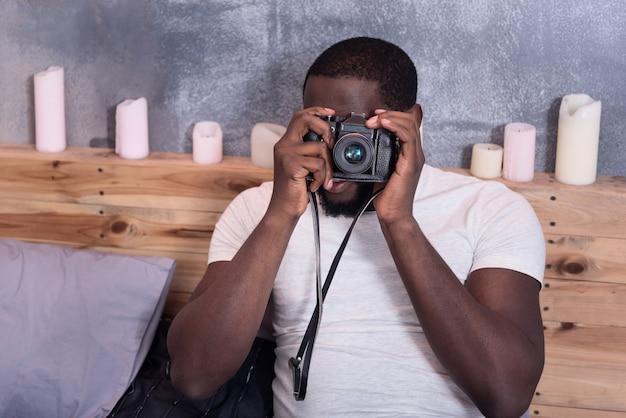 ベッドに横になってカメラを持って写真を撮る集中青年。