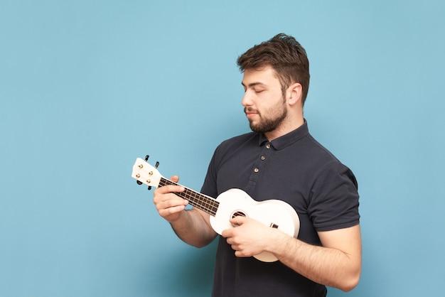 濃い色のtシャツを着た集中力のある若い男が手にウクレレを付けて青に立ち、弦を注意深く見ています。