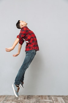 Concentrated young man jumping over grey wall.