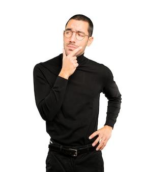 Сосредоточенный молодой человек делает жест недоверия