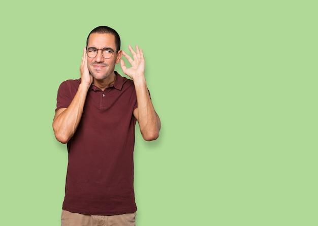 Сосредоточенный молодой человек делает жест, пытаясь что-то услышать