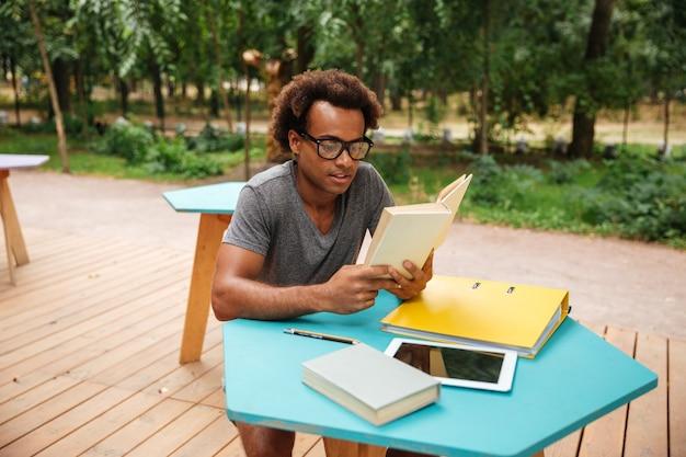 집중된 젊은 남자 앉아서 야외에서 책을 읽고