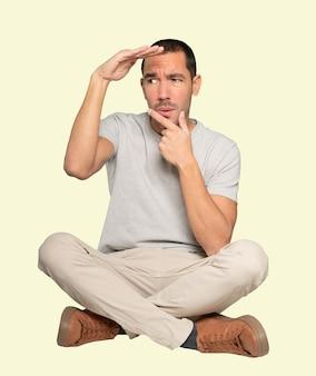 Сосредоточенный молодой человек с жестом отводит взгляд