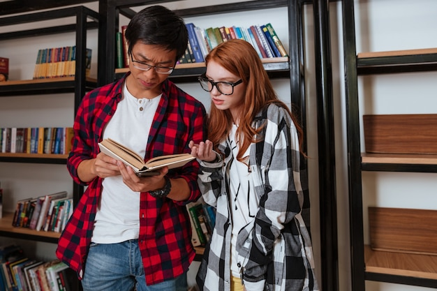 Concentrated young man and woman standing and reading book in library