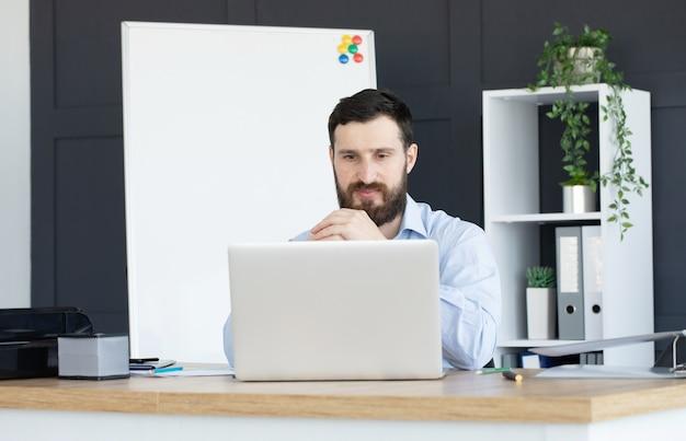 Концентрированный молодой человек, работающий на ноутбуке в домашнем офисе