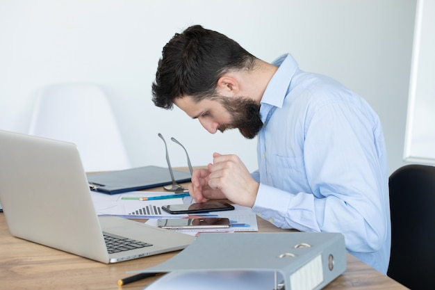 집에서 사무실에서 노트북에서 일하는 젊은 남자를 집중