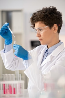 Concentrated young microbiologist in lab coat using pipette while dropping reagent into test tube