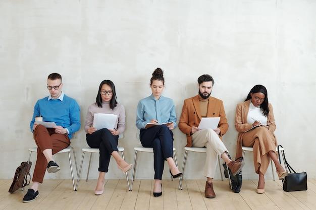 廊下で書類を持って座って面接の前にそれを調べる仕事のための集中した若い多民族の候補者