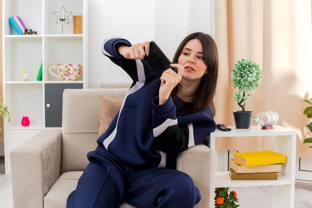 Concentrato giovane donna abbastanza caucasica che si siede sulla poltrona nel salotto progettato che gioca gioco sul telefono