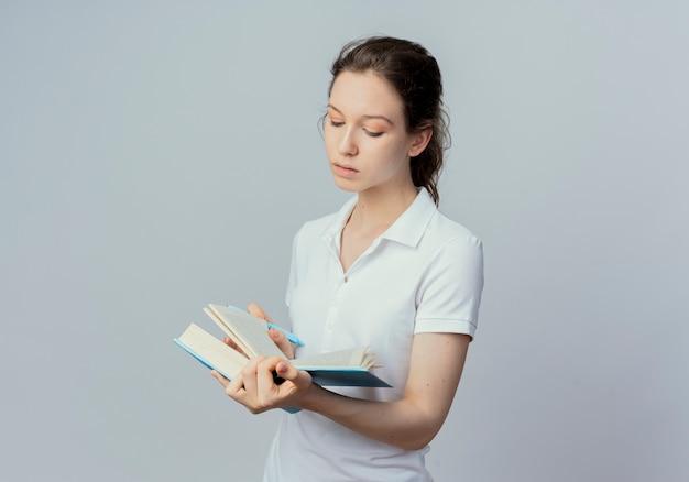 Концентрированная молодая симпатичная студентка держит и читает книгу с ручкой в другой руке, изолированной на белом фоне с копией пространства