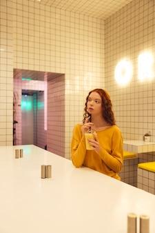 Signora riccia concentrata della giovane testarossa che si siede in caffè