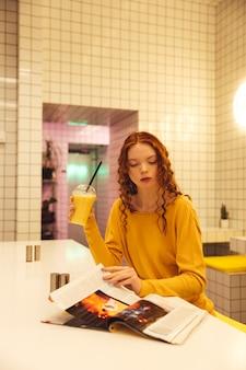 Сконцентрированная молодая рыжая кудрявая дама сидит в кафе