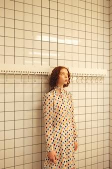 カフェに立っている若い赤毛の巻き毛の女性を集中