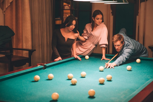 Concentrated young redhead man aiming into billiard ball. he look straight forward. young woman in pink dress sit at billiard table. asian brunette stand beside them. women look at game.