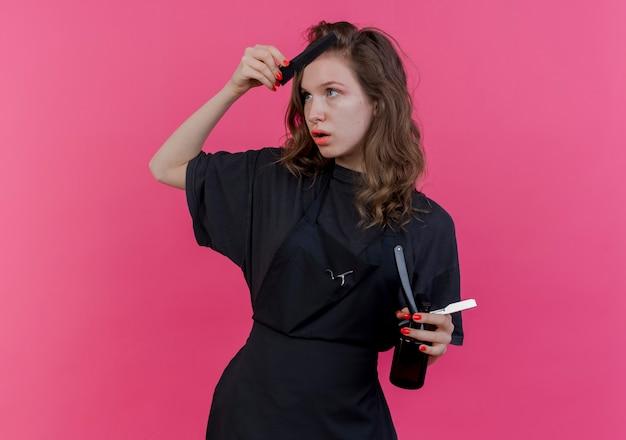 집중된 젊은 슬라브 여성 이발사 제복을 입고 머리를 빗질하고 복사 공간이 분홍색 배경에 고립 된 측면을보고 스프레이 병으로 면도칼을 들고