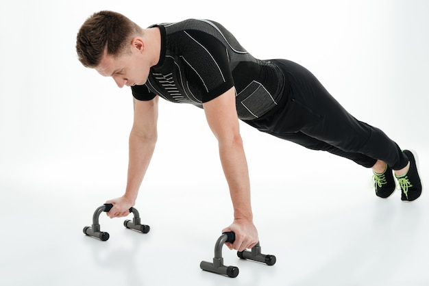 Concentrated young sportsman doing push ups with gym equipment