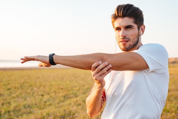 Сосредоточенный молодой спортсмен протягивает руки и слушает музыку в наушниках на открытом воздухе