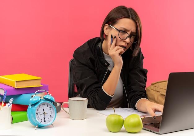 Concentrato giovane studente ragazza con gli occhiali seduto alla scrivania tenendo la penna mettendo la mano sul viso utilizzando laptop isolato in rosa