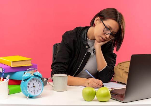 Concentrato giovane studente ragazza con gli occhiali seduto alla scrivania scrivendo con la penna sul blocco note facendo i compiti mettendo la mano sul viso isolato sul rosa
