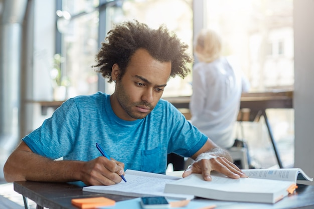 Concentrated young student male in blue t-shirt sitting at desk indoors rewriting information from book in copy book. attractive dark-skinned man writing sinopsis while sitting at cozy cafeteria