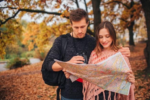 Сконцентрированные молодые туристы стоят в парке и смотрят на карту. она держит это и улыбается. люди в парке.