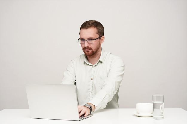 彼のラップトップでテキストを入力し、白い背景の上に座って、画面上で注意深く見ている眼鏡の集中した若い剃っていない短い髪の男性
