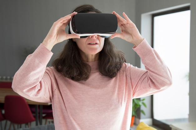 Concentrated young woman adjusting virtual reality goggles