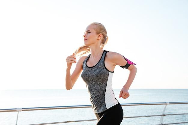 운동을 하고 부두에서 달리는 집중된 젊은 여성 운동선수