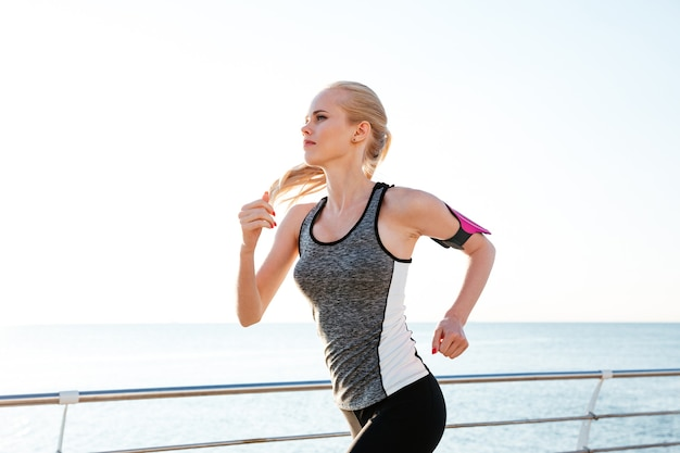 Concentrated young woman athlete working out and running on pier