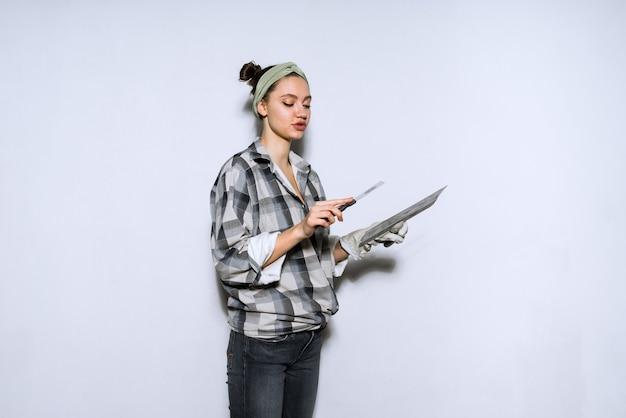 Концентрированная молодая женщина-строитель делает ремонт, шпаклевка стен