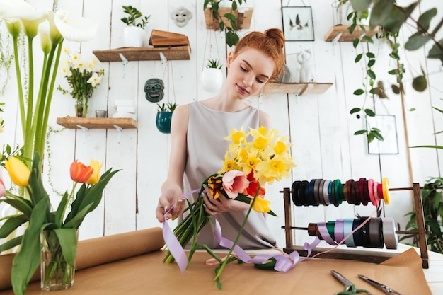 Concentrated young woman collecting colorful bouquet in workshop