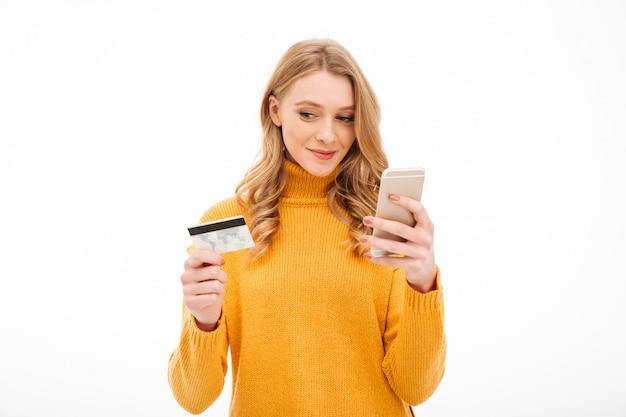 Сконцентрированная молодая женщина держа мобильный телефон и кредитную карточку.
