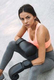 야외에서 콘크리트 바닥에 앉아 운동복과 권투 장갑에 집중된 젊은 여자