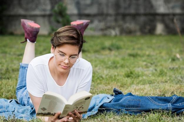 Концентрированная молодая женщина, чтение лежа на газоне Бесплатные Фотографии