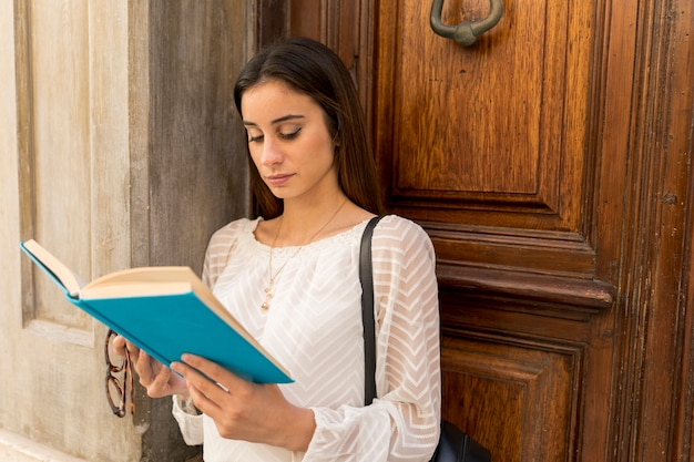 Concentrated young woman reading near wooden doors