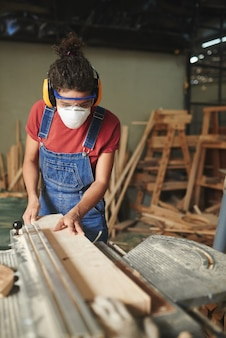 Concentrated young woman in safety glasses, mask and earmuffs cutting wooden board on table saw