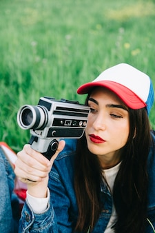 Concentrated young woman using vintage camera