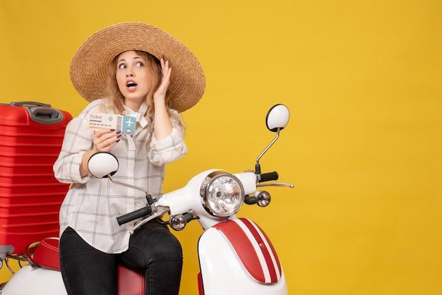 모자를 쓰고 오토바이에 앉아 노란색에 마지막 가십을 듣고 티켓을 들고 집중된 젊은 여성