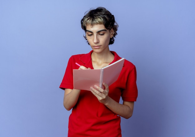 Concentrated young woman with pixie haircut writing something on note pad with pen