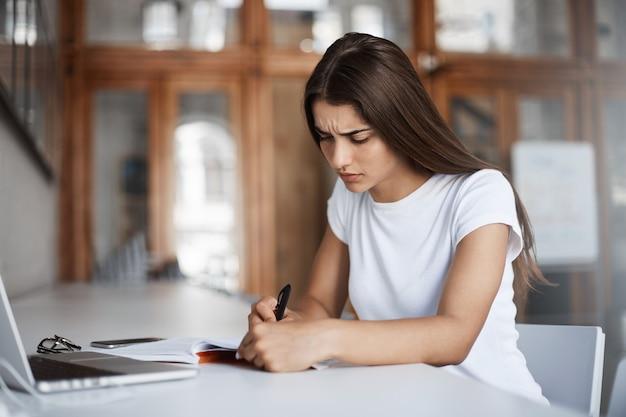 Сосредоточенная молодая женщина пишет письмо в блокноте, не используя портативный компьютер, чтобы собраться с мыслями.