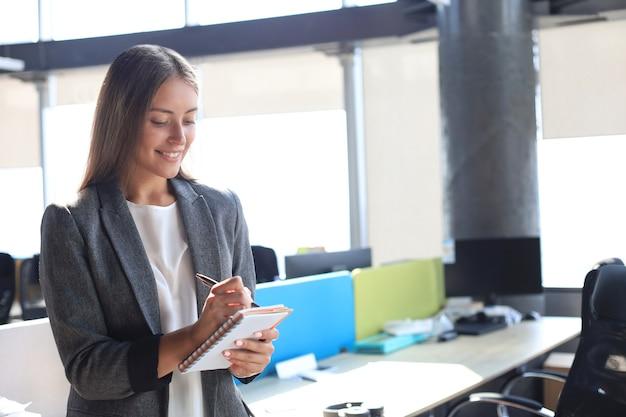Сосредоточенная молодая женщина что-то записывает, работая в офисе.