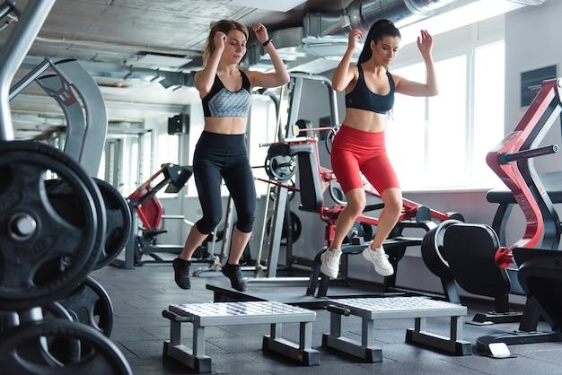 現代のジムのプラットフォームで同期してジャンプするスポーツウェアの集中した若い女性