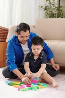 아버지와 함께 바닥에 앉아 다채로운 블록으로 탑을 쌓는 집중된 아이