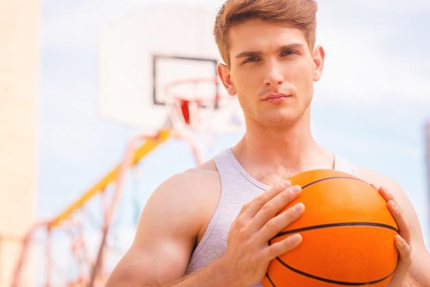 경기 전 집중. 총을 쏠 준비가 된 잘생긴 젊은 남자 농구 선수