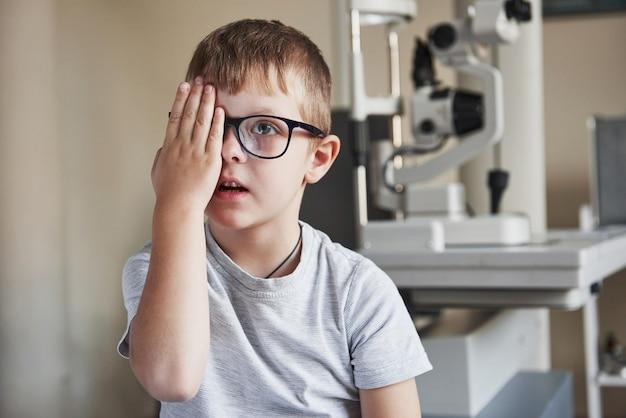 Концентрация на изображениях. маленький мальчик прикрывает глаз и проверяет зрение в клинике.