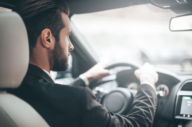도로에 집중하고 있습니다. 차를 운전하는 동안 똑바로보고 젊은 잘 생긴 남자의 후면보기