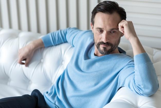 考えに集中する。ソファに座って額に触れる素敵な気持ちの良い思いやりのある男